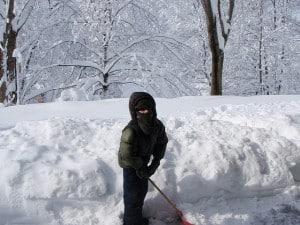 Child shoveling snow.